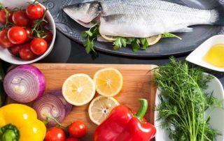 Potravinové doplnky: Ryba s citrónom, avokádom, olivovým olejom na drevenej doske